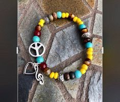 Excited to share this item from my #etsy shop: Peace, Love & Music Bracelet. Womens Bracelet/Gift for her/ Mens Bracelet. Gift for him. BOHO Bracelet. Boho Chic. Good Vibes. Music. Love #blue #yellow #no #unisexadults #bohohippie #heartcharmbracelet #trebleclef #musicjewelry #bohochic #peacesign #peacejewelry #hippiejewelry #musiclovers Music Jewelry, Hippie Jewelry, Hippie Boho, Bohemian, Crochet Necklace, Beaded Necklace, Treble Clef, Blue Yellow, Gifts For Him