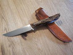 Hier mal wieder ein Messer mit einem äußerst außergewönlichen Griff.  Bei diesem Jagdmesser mit einer 11,5 cm langen Klinge aus Böhler N690 habe ich die Griffschalen aus stabilisiertem Kaktus gefertigt.  Die Zwischenräume sind mit rotem, schimmernden Harz gefüllt, ein Supereffekt.  Die Gesamtlänge beträgt 23,8 cm, zu dem Messer gehört die von mir handgefertigte Lederscheide.