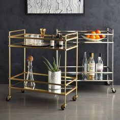 "$400 Terrace Bar Cart in bronze or nickel. Cocktail station inspired by 1930's Art Deco design. 4 wheels. 27.8""w x 14""d x 31.75""h. Glass top shelf; mirrored bottom shelf. Metal frame. Set on wheels."