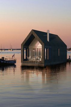 """This """"Floating Barn"""" designed by Latvian architects is actually a floating two-story home, functioning as both boat and lake house."""