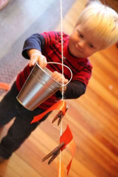 A simple clothesline activity for toddlers to play with! Add a bucket to haul and dump objects and clothespins for fun fine motor practice!