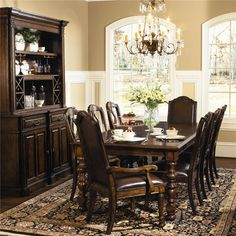 This beautiful formal dining set will blend nicely with your traditional home decor. The smooth rectangular top has a beveled edge, and a distinctive crossing pattern on top with rich contrasting pine and walnut veneers. Two 18 inch leaves allow you to extend the table to 114 and a half inches when guests arrive. Cool turned wood legs add lots of character to this table. The side chairs and arm chairs feature high backs with a curved crown, and a rich wood frame.