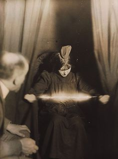 Séance c. 1912  Electric ectoplasm and a strange object on the head of the medium. Reproduced image.