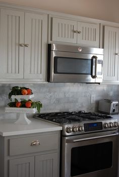 Gray lowers with lighter uppers and marble backsplash. Classy!