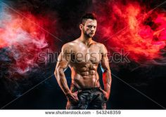 Strong bodybuilder with six pack. Man with perfect abs, shoulders,biceps, triceps and chest, personal fitness trainer flexing his muscles in blue, red smoke