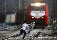 A refugee boy runs across rail tracks as a train approaches at Greece's border with FYRO Macedonia, /Yannis Behrakis