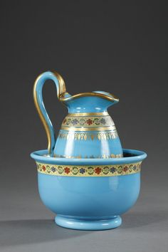 A bowl and its egg-shaped jug in blue turquoise opal crystal, decorated with gold, silver, blue and red coloured friezes of anemones and forget-me-not on gilded background...