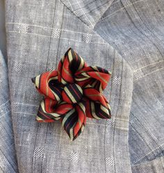 A colorful silk lapel flower pin made in the Japanese tsumami kanzashi style for modern guys and women! I used a burnt orange, gold, and blue-black striped kimono silk to make the flower, glued a cover button into the center, and mounted everything on a tie tack finding. Complements a blazer, sport jacket, suit, suspenders, cardigan, overcoat, vest, or hat. Kanzashi flowers are made from folded fabric squares, one petal at a time. Originally, apprentice geisha made kanzashi hair accessories…