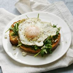 Crispy fried egg on artisan toast with arugula, feta cheese, and a homemade herb oil drizzle.
