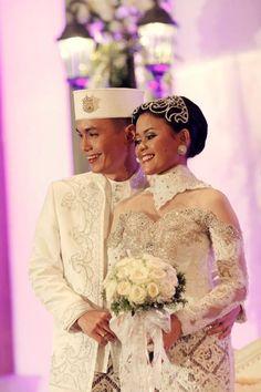 Peci berwarna putih dengan hiasan cantik membuat pengantin pria terlihat elegan tanpa meninggalkan unsur tradisional.