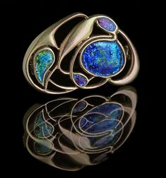 ARCHIBALD KNOX 1864-1933 Liberty & Co Art Nouveau Brooch  Gold Enamel H: 2 cm (0.79 in)  W: 3 cm (1.18 in)  Marks: 'Cymric' & '9ct' British, c.1900