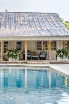 A blue pool leads to a covered brick patio of the pool house, which features wood columns across the front and an aged metal roof and brick chimney Future House, Barn Pool, Pool Barn House, Pool House Designs, Pool House Plans, Plantation, The Ranch, Alabama, House Tours