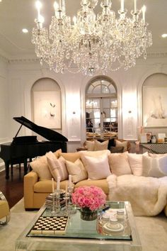 An over-the-top chandelier paired with a grand piano makes for a luxe interior pairing.   - HarpersBAZAAR.com