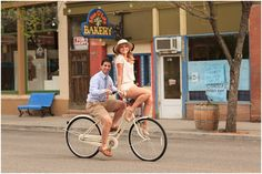 Photo of couple riding cruiser bike in old downtown Palisade, Colorado for engagement session