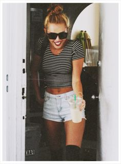 This is one of my biggest fashion inspirations Miley Cyrus. Here she is wearing a very casual but cute outfit. She wears her striped american apparel crop top with light denim shorts and high socks. It looks great and vintage but the real nice touch her is her top not bun in her hair. The tight bun makes her look very classy and the sunglasses help her to look super chic.