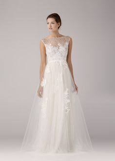 A-line lace applique wedding dress. French cotton lace is appliquéd onto a sheer tulle bodice with a high neckline front and low V-cut back.