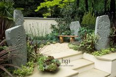 Courtyard small garden with drought-tolerant planting sandstone monoliths ornament focal point stone wooden bench seat chair Eucalyptus tree Cordyline Helichrysum petiolare Lavandula Lavender gravel stones Melianthus steps retaining wall raised bed change in level Designer Zoe Cain for St Joseph's Hospice RHS Chelsea Flower Show 2008 UK Marcus Harpur