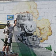 Keith Hasenbalg painting the train into the mural at 130 S. Detroit in downtown Xenia. Xenia Ohio, Water Tower, Murals, Repeat, Detroit, Graffiti, Street Art, Sleep, Bike