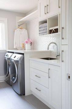 Laundry Room Organization Ideas. Folding Counter. Mud Room Sink. Glass Tile Backsplash. White Built-in Cabinets. Drying Rack.