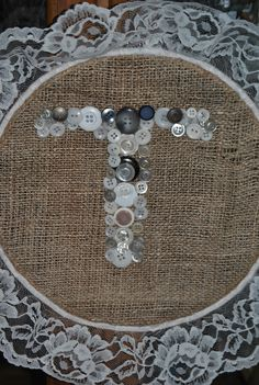 """For my Daughter's Rustic Vintage Wedding...used the embroidery rings, a piece of burlap, hot glued lace around edges, and used vintage buttons to make a """"T"""", added a piece of jute string to the top and voila! you can hang anywhere or use as a prop on table, whatever....cost me approx One dollar each to make them."""
