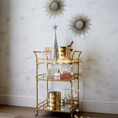 Serve in style with our tiered bar cart. With two clear glass storage shelves and a mirrored bottom shelf that accommodates tall bottles, its wrought iron frame and golden finish give happy hour a luxe look. Diy Bar Cart, Gold Bar Cart, Bar Cart Styling, Bar Cart Decor, Bar Carts, Outside Bars, Home Bar Decor, Serving Cart, Glass Shelves