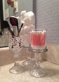 Candle stick holder w/glass cup glued together.  Genius and very pretty!  Also love the glass beads for the makeup brushes.