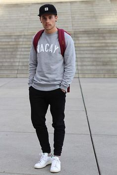 Consider teaming a grey graphic crew-neck sweater with black track pants for a trendy and easy going look. White low top sneakers are a good choice to complete the look.   Shop this look on Lookastic: https://lookastic.com/men/looks/crew-neck-sweater-sweatpants-low-top-sneakers/18933   — Black Baseball Cap  — Burgundy Backpack  — Grey Print Crew-neck Sweater  — Black Sweatpants  — White Low Top Sneakers