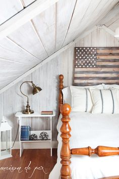 Wood american flag above bed. Love this cottage cozy space!