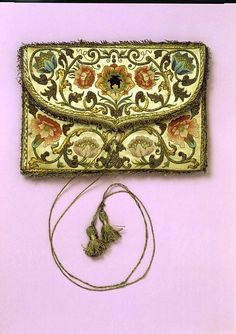 The Lee Embroidered Purse, 1700-30 | Pochette of polychrome silk and metallic wire embroidery. It is adorned with a braid in satin stitch and French knots.  The front flap sports two exceptional tasseled strings of silver-gilt thread. The front features a formal design of flowers on scrolling stems while the reverse depicts a shield of arms with a horizontal bar and three crescents on a field adorned with stars surrounded by a floral border.