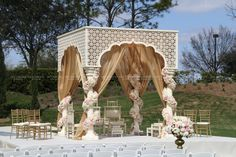 This classical-style pillar mandap with golden draping and floral garlands looks stunning as it flutters in the breeze. Wedding Entrance, Wedding Mandap, Entrance Decor, Pergola With Roof, Outdoor Pergola, Gazebo, Mandap Design, India Wedding, Wedding Stage Decorations
