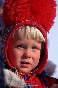 Sami boy in traditional red pom-pom hat at a Spring festival in Kautokeino, North Norway     Sami