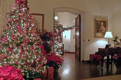 A glittering 13-foot tree skirted with poinsettias greets visitors as they enter the living room. A portrait of Nell DeGolyer hangs above a baby grand piano.