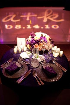 the reception sweethearts table decorated with purple linens, silver dishes, and purple and white flowers - photo by Washington DC wedding photojournalist Paul Morse