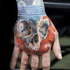 Orange With Blue Wrist Band Mens Skull Hand Tattoo Designs