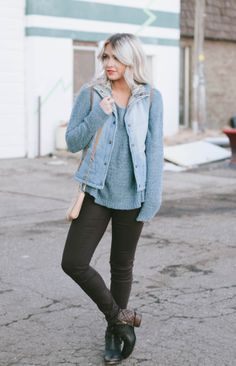 blue sweater, blue puffer vest, black jeans, and black and brown ankle boots