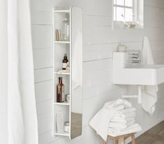 A white wall mirror with shelves behind that stores bottles and creams.