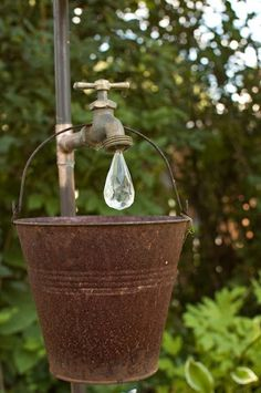 A rusty bucket hanging from an old tap with a crystal hanging from the spout to represent a large drop of water... priceless!
