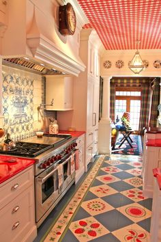 Red countertops, strawberry motif painted floor, gingham ceiling, fun kitchen!