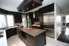 Moderd Kitchen with Maple cabinets stained espresso and two tone quartz countertops.
