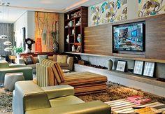 No living de 80 m², a proposta é de um espaço multifuncional e aconchegante. A estante de madeira se prolonga num painel sustentado por prateleiras que abrigam a lareira  Arquivo / Casa e Jardim
