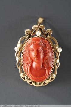 Broche-pendentif en or et camée corail Broche ovale décorée d'une camée en corail rouge représentant un buste féminin vu de face, la chevelure détachée. Monture en or ajourée et ciselée, ornée de perles. Ce bijou peut également se porter en pendentif. Circa : 1860