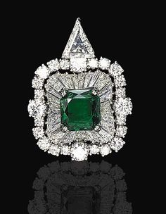 AN EMERALD AND DIAMOND PENDANT   Centered by a rectangular-cut emerald within a baguette-cut diamond ballerina mount surrounded by circular-cut diamonds, suspended from a detachable triangular-cut diamond bail, mounted in platinum
