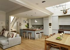 This neutral, bespoke Roundhouse kitchen features handleless draws and a stylish, timber breakfast bar