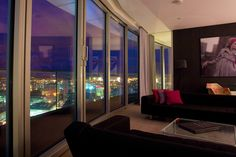 huge penthouse suite in a glitzy hotel, walls of floor to ceiling windows with a panoramic night view of the city...