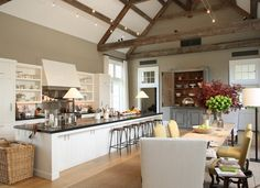 I believe this is Ina Garten's kitchen. This is one of my all time favorite kitchens. Open shelving, huge island and long farm house table. Ahh... a girl can dream