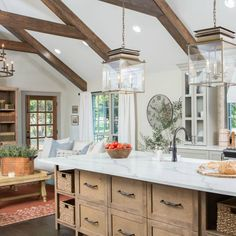 A Fixer Upper farmhouse kitchen by Joanna Gaines with French Country an European country decor.  Hanging Lanterns Island Copper vessel Coffee Table natural books French Door