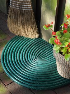turn old leaky hose into a door mat, you can just hose it off! perfect for the back door before coming inside!