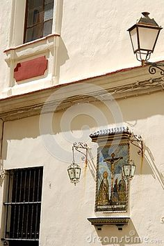 Photo made at Cadiz in Andalusia (Spain). The picture shows part of the facade of a house of character. The image consists of a street lamp fixed to the wall, a small painting with a religious theme with small brick roof and two small side street lamps, two windows, one with bars.