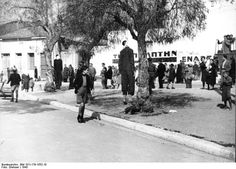 Occupied Greece, 1943: Two people hang from trees in the square of an unidentified village. Village people loiter around without much particular horror. Note the young boy that is walking past the scene in the foreground -- well dressed and groomed for the time, he is adjusted to the realities of the day.