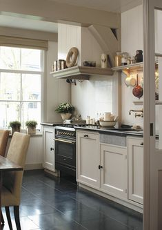 Modern country kitchen cupboards and black hardware; nice shiny black floor, too